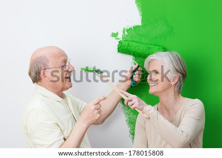 Playful senior couple painting their house green with the man laughingly pointing a finger at his wife a she tries to dab paint on his nose with her brush - stock photo