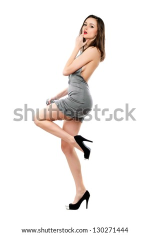 Playful sexy brunette wearing grey dress and black shoes. Isolated on white - stock photo