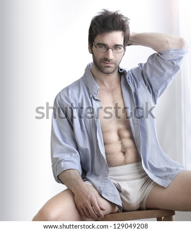 Playful sexy portrait of a handsome buff man in underwear and open business shirt with sensual expression against white - stock photo