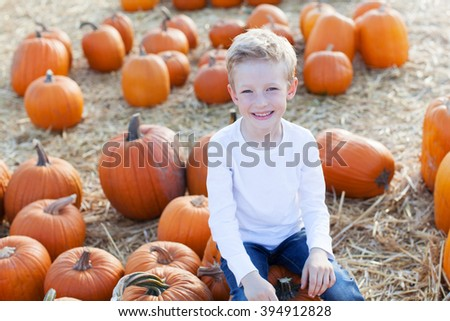 playful smiling boy enjoying autumn time at pumpkin patch