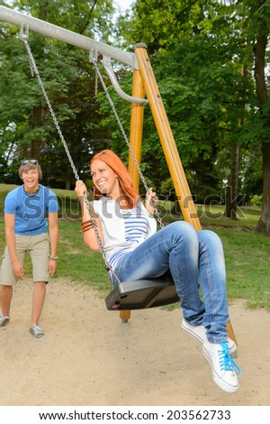 Playful teenage couple girl sitting on swing in park