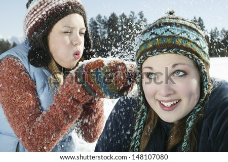 Playful teenage girl blowing snow on her friend in winter - stock photo
