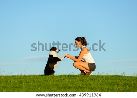 Playful woman and cute dog having fun and enjoying leisure outdoor. Sporty girl training her pet and playing around. - stock photo