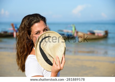 Playful woman covering her mouth with straw hat at Railay Beach, Krabi, Thailand. Brunette girl joking and having fun on vacation travel. - stock photo