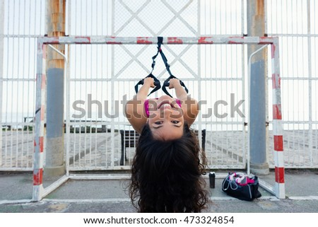 Playful woman having fun and enjoying trx workout with fitness straps.