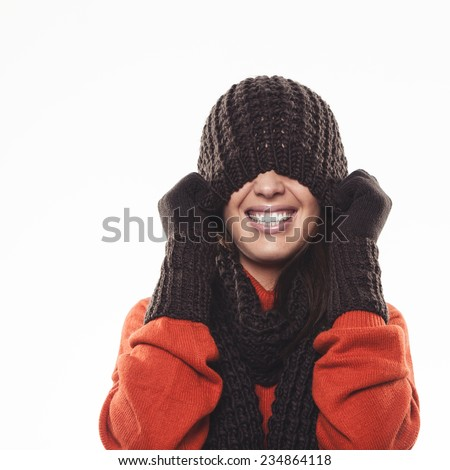 Playful woman hiding under a knitted brown winter hat pulling it down over her eyes with a laughing smile, isolated on white