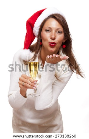 Playful woman wearing a festive red Santa hat and holding a flute of champagne celebrating Christmas blowing a kiss across the palm of her hand with a mischievous smile, on white - stock photo