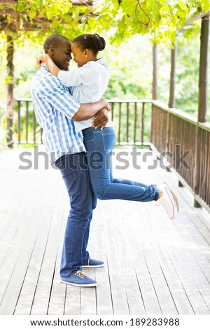 playful young african couple hugging under grape vines - stock photo