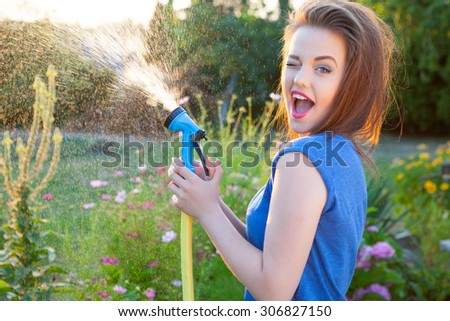 Playful young attractive winking woman with water hose watering plants, gardening concept - stock photo