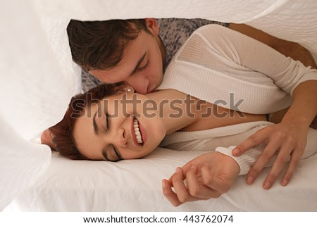 Playful young beautiful couple laying together under white linen in bed, hugging and kissing with romance and desire, home interior. Boyfriend and girlfriend lovers in bedroom, indoors lifestyle. - stock photo