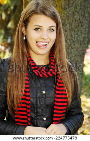 Playful young beautiful woman showing tongue in the park - stock photo
