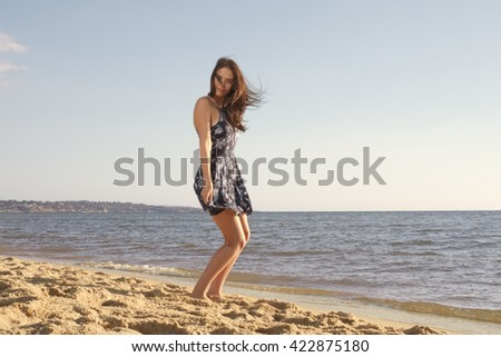 Playful young beautiful woman standing in short dress on the sandy beach while wind waving her hair