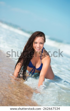 Playful young brunette posing on the beach - stock photo