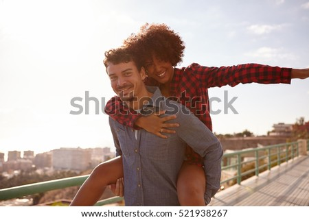 Playful young couple playing aeroplane her left arm out and holding onto his chest with her right arm while getting a piggy back ride