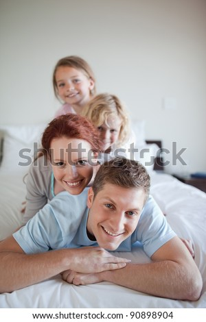 Playful young family together on the bed