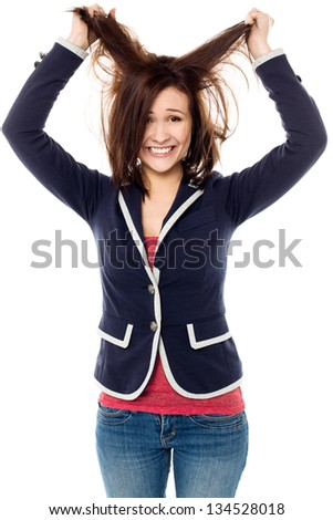 Playful young female pulling her hair out in madness. - stock photo