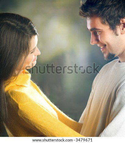 Playful young happy smiling attractive couple embracing, outdoors - stock photo