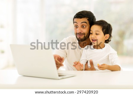playful young indian man using laptop with his son at home - stock photo