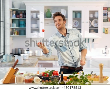 Playful young man juggling with tomatoes in kitchen, smiling.