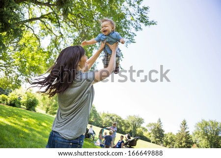 Playful young mother lifting baby boy with friends and children in background at park - stock photo