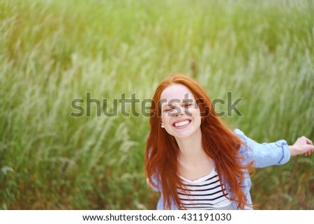Playful young redhead woman frolicking in a spring field dancing around with outstretched arms grinning at the camera, with copy space - stock photo