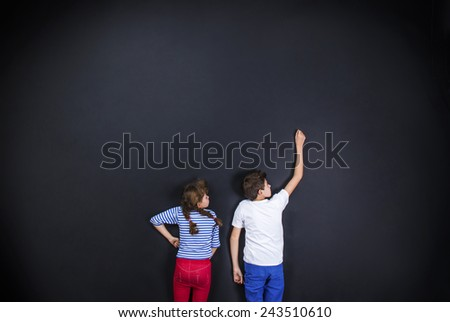 Playful young siblings having fun together as they prepare to go back to school. Studio shot on a black background. - stock photo