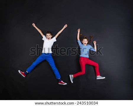 Playful young siblings laughing and having fun together. Studio shot on a black background. - stock photo