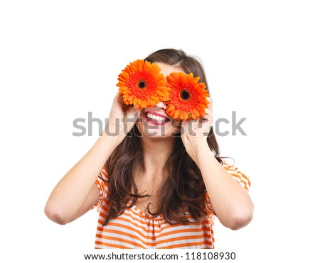 Playful young woman covering her eyes with flowers - stock photo