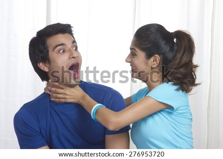 Playful young woman gripping man's neck at home