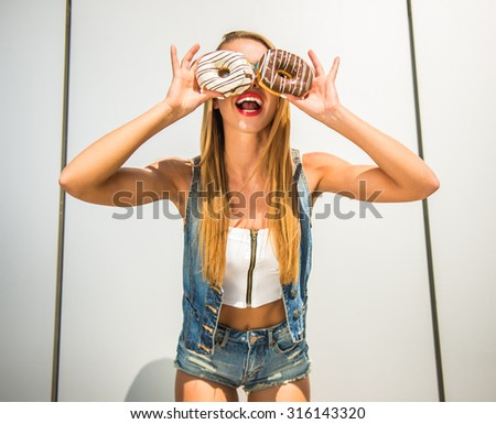 Playful young woman holding donuts against her eyes and smiling while standing against the wall. - stock photo