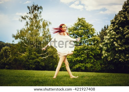 Playful young woman in a park on the meadow - stock photo