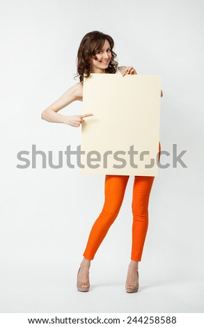 Playful young woman in orange pants holding blank placard showing at it, full length portrait on neutral background - stock photo