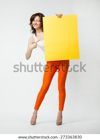 Playful young woman in orange pants holding blank yellow placard showing at it, full length portrait on neutral background - stock photo