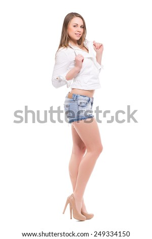 Playful young woman posing in white shirt and denim shorts. Isolated on white