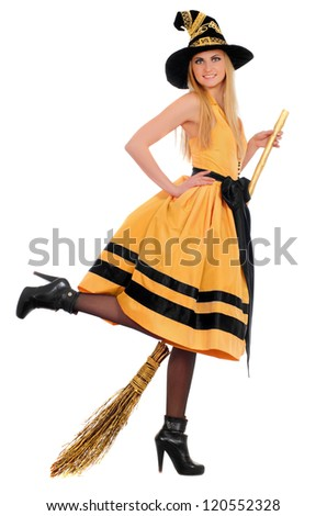 Playful young woman with a besom wearing costume witch. Isolated