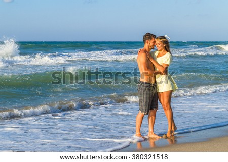 Playfull young couple in dress and shorts at the beach. - stock photo