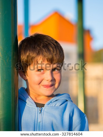 Playground in winter sunny day. Beautiful six year old boy laughs and hides