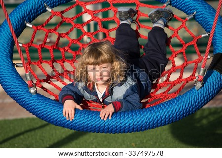 Playground in winter sunny day. Little boy swinging on a swing - stock photo