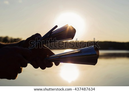 Playing a musical instrument agogo on background sky at sunset - stock photo