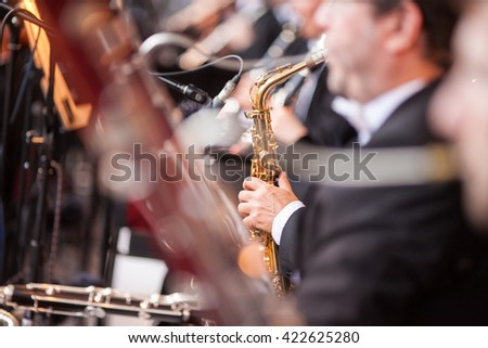 Playing a saxophone. Sound orchestra close up. Saxophone close up. Musician playing a saxophone. Musical concert.