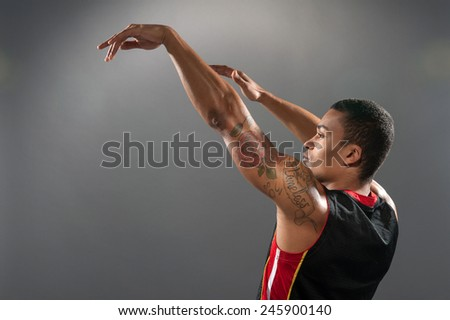Playing baskerball. Young African basketball player throwing the ball and raising his hands up to copy space while standing against grey background - stock photo
