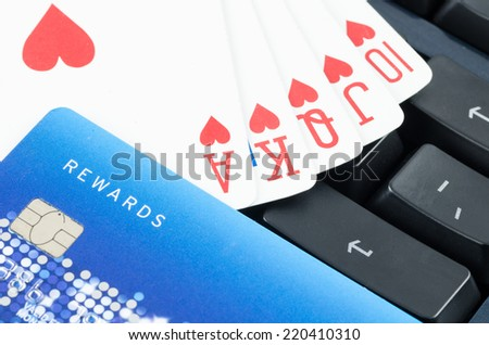 playing card and credit card on the computer keyboard, Online gamble concept - stock photo