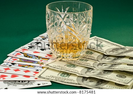 playing cards and money on the green cloth