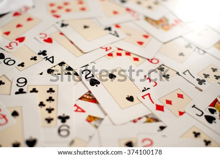 Playing cards background with a random arrangement of cards covering a table viewed low angle with shallow depth of field and focus to the two of spades - stock photo