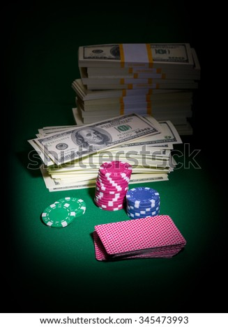 Playing cards chips and dollars on green table