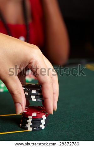 Playing cards, chips and players gambling around a green felt poker table. Shallow Depth of field, focus on red chips