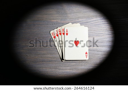 Playing cards in light on wooden table, top view - stock photo