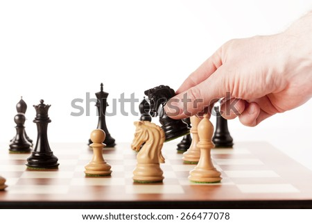 Playing chess ,a hand moving black knight on a chessboard - stock photo