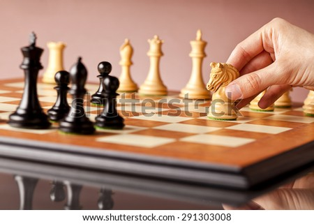 Playing chess - a male hand moving white chess knight on a traditional wooden chessboard - stock photo