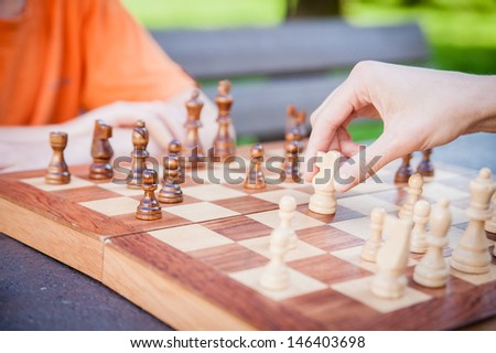 Playing chess, hand moving piece - stock photo